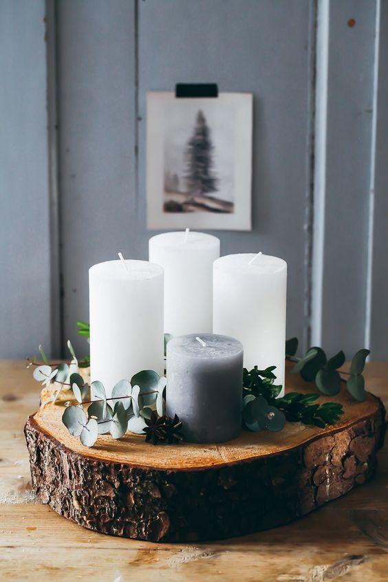 des bougies sur un rondin de bois pour attendre Noel